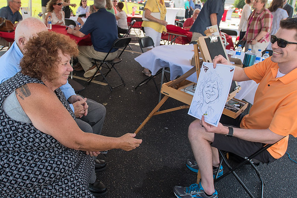Casey Christenson (right) shows his finished caricature of Mary Kelly (left) to her at a Greater Mankato Growth event. Christenson now draws caricatures full time. Photo by Jackson Forderer