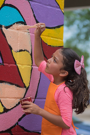 Clarissa Lira, 6, paints a section of a mural on the wall of Bellissimo Paint and Coatings along Riverfront Drive on Saturday. Photo by Jackson Forderer