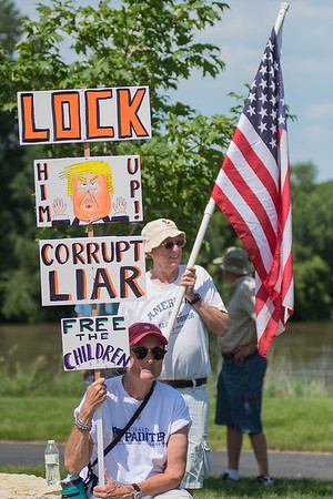 "Ann Judkins holds a protest sign and Leigh Pomeroy holds an American flag while attending the Keep Families Together rally held at Riverfront Park on Saturday. Pomeroy said the reason he brought a flag was because ""too often the flag has been co-opted by people we feel don't represent American interests."" Photo by Jackson Forderer"