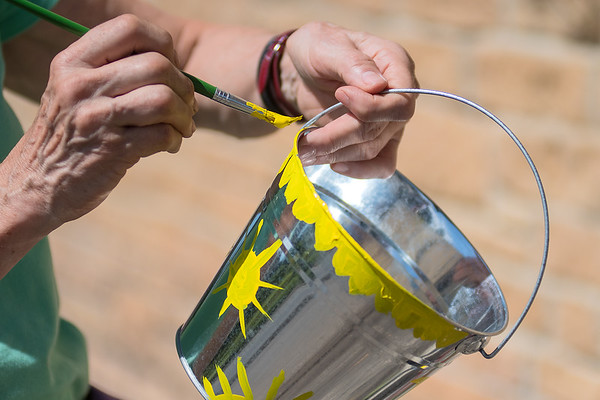 Penny Banwart paints a bucket that will be used by those who come to Holy Grounds at Centenary United Methodist.  Photo by Jackson Forderer