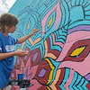Charlotte Maxfield, 9, paints in a section of a mural going up on the outside of Bellissimo Paint and Coatings on Riverfront Drive on Saturday. The mural was open to the public to be painted. Photo by Jackson Forderer