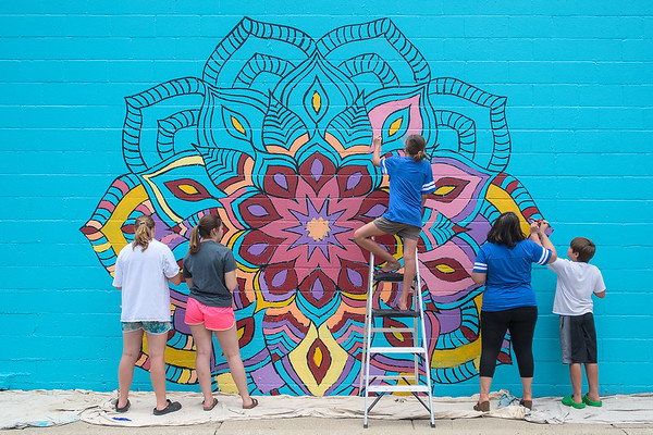 People work on the mural outside of Bellissimo Paint and Coatings on Riverfront Drive. The mural consists of four large flower designs and the public was invited to paint sections of the mural. Photo by Jackson Forderer