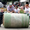 The Janesville Jacks and Jills roll a hay bale toward the finish line during the first farm chore olympics at the Waseca County Fair.