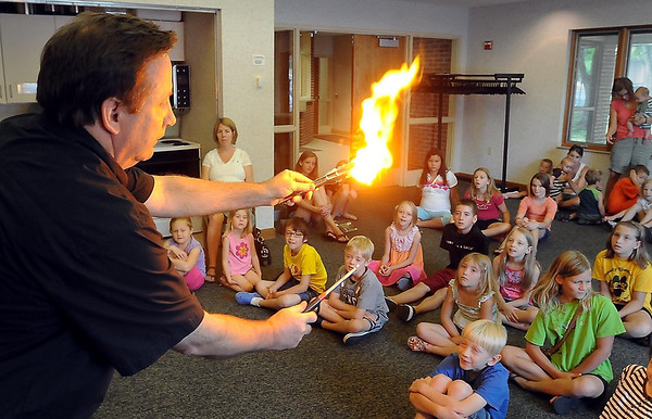 John Cross<br /> Jim Birkel gives youngsters a dramatic demonstration of the effect of smoking on a family budget Wednesday by lighting a fake dollar bill on fire during a Mad Science presentation, part of the North Mankato Taylor Library's summer reading program.