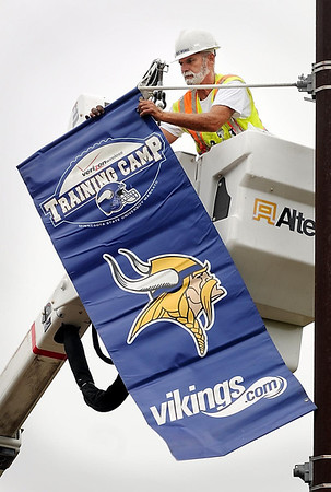 John Cross<br /> Mankato city worker Kenny Braam hands up Vikings training camp banners along Stoltzman Road Thursday in preparation of the teams return to Minnesotta State University. Players report for camp next Thursday.