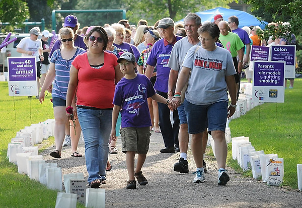 John Cross<br /> Cancer survivors and their families take a lap along a path lined with luminaria honoring those whose lives have been touched by the disease at the Blue Earth County Relay for Life Friday at Ray Erlandson Park.