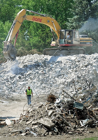 John Cross<br /> A worker is dwarfed by the mountain of rubble from what once was one of the Gage Towers at Minnesota State University. Backhoes began this week to sort and clear demolition materials after the 12-story skyline landmarks were imploded June 29.