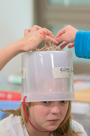 Ava Schneider, 12, watches her friends put Army men on top of her impromptu bucket hat at Prairie Wind Middle School during Connections camp. Photo by Jackson Forderer