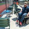 "John Aaker, a board member for the SMILES Independent Living Center, shows how that even with removable seats along the first base line at Franklin Rogers Park, the tables are not handicap accessible due to the metal peg still being in the way. ""It was a little shocking to us,"" Aaker said, ""that they would (ask for an audit) at the end."" Photo by Jackson Forderer"