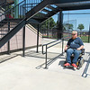 "John Aaker, a board member with SMILES Independent Living Center, comes down from the ramp connecting the main seating area to the plaza at Franklin Rogers Park. ""They had it all completed and then a month or two ago they asked for an audit,"" Aaker said, ""It would've been easier in the beginning."" Photo by Jackson Forderer"