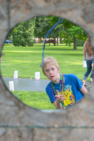 Will Hiller, 12, throws a beaded necklace at a board in a game set up along the path at Relay for Life held on Friday at Sibley Park. Photo by Jackson Forderer
