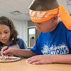 Zoie Carrasco (left), 11, watches Cooper Behnke, 11, pick out red, white and blue beads as the two worked on art projects at Connections camp at Prairie Winds Middle School on Tuesday. Photo by Jackson Forderer