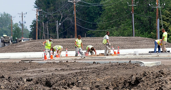 Workers pour concrete at one of the roundabouts along Blue Earth County Road 17 near Eagle Lake Thursday afternoon. Photo by Pat Christman