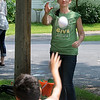 Elizabeth Lintelman plays catch with a boy at the Lime Valley Mobile Home Park while volunteering with the Salvation Army's Mobile Outreach during Rasmussen Community Give Back Day Friday. Photo by Pat Christman
