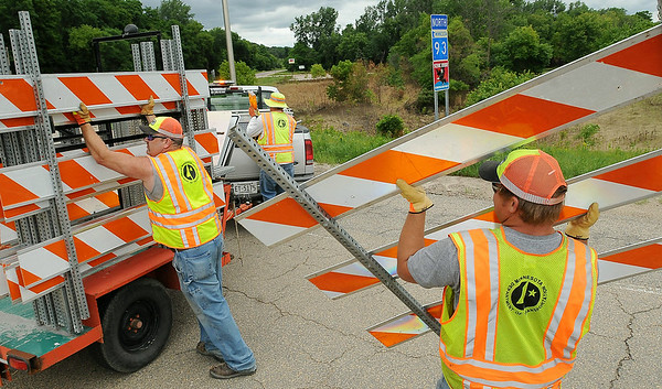 MnDOT crews remove barricades at the intersection of Highway's 93 and 169 Monday afternoon. The road to Henderson has been closed since June 19 because of heavy flooding. Highway 19 from Highway 169 to Henderson remains closed as crews remove debris and rebuild sections of the road that washed out as a result of the flooding. Photo by John Cross