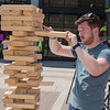 Caleb Curran plays a game of Jenga in-between foosball games. Curran played on the Bolton and Menk human foosball team. Most players grabbed some shade and got out of the heat between games. Photo by Jackson Forderer