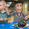 Ramona Clemons (right), 5, attaches a wire to an eggplant at the Children's Museum loft on Tuesday. Ramona along with her brother Julius Clemons, 3, attached the wire to different objects to make different sounds with the electrical board. Different activities in the loft center on the theme of electricity this week at the loft. Photo by Jackson Forderer