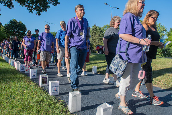 Participants in the Relay 4 Life fundraiser walk along a path in Erlandson Park lined with bags showing victims and survivors of cancer. Those wearing purple are cancer survivors. The even raises funds for the American Cancer Society. Photo by Jackson Forderer