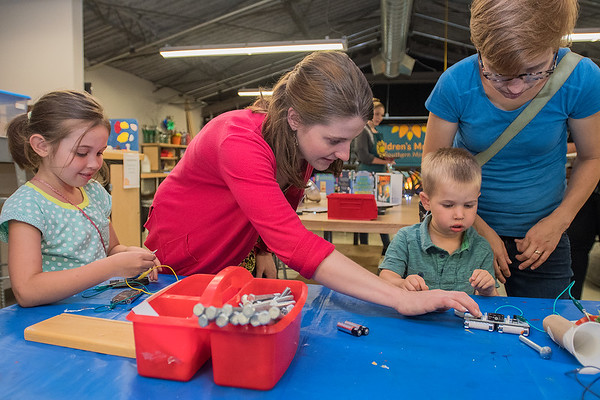 Mia Forslund (second from left) shows Julius Clemons (second from right), 3, and Olive Clemons (left), 7, how to make sounds with an electric panel at the Children's Museum of Southern Minnesota loft on Tuesday. Photo by Jackson Forderer
