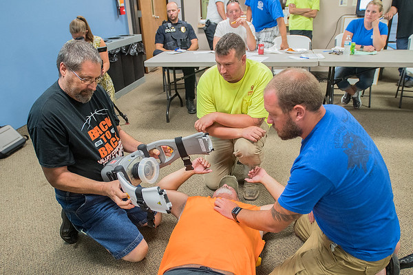 From left, Keith Kunkel, Andrew Javens and Bob Strand practice using a automatic chest compressor on fellow Madison Lake firefighter Matt Moniz at City Hall on Wednesday. Photo by Jackson Forderer