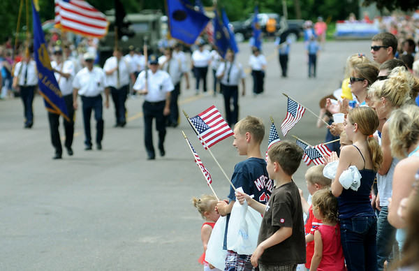 A patriotic crowd watches approach of one of the color guards in Elysian's Fourth of July parade. Photo by John Cross