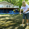 Sandbags still surround the Waterville resident Marsha Guibbert's home on Lake Tetonka as she rakes algae and mud from the yard. She said rising waters just reached the edge of the sandbags before receding and caused no damage to her home. The blue tarps hanging beneath the deck are from deck-staining chores and were unrelated to the flooding. Photo by John Cross