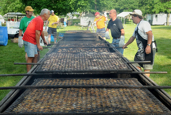 Volunteers from the St. Peter Ambassadors tend to the 900 hundred chicken dinners they cooked over charcoal for St. Peter's Old Fashioned Fourth of July.