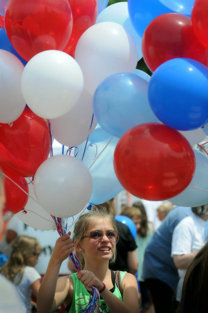 Alaura Niedosmialek of Morristown carries a patriotic bouquet of balloons at Elysian's Fourth of July celebration. Photo by John Cross