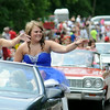Pageant contestants greet parade watchers with synchronized waves during Elysian's Fourth of July parade. Photo by John Cross