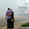 A Waterville couple displaced by a fire in the Rogers Building  embrace on a smoke-filled street on Thursday. Photo by John Cross