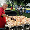 St. Peter Ambassador Greg Seitzer seasons up some of the 900 chicken quarters before they were placed on the grill at Minnesota Square in St. Peter on Friday. Photo by John Cross