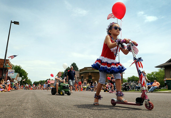 Youngsters cruise down Elysian's parade route during the Kiddie Parade during the community's Fourth of July celebration. Photo by John Cross