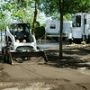 Water still surrounds some RVs as Jim Rinehart spreads recycled asphalt over previously flooded parts of the Willow Creek Park in Waterville. Photo by John Cross