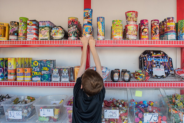Isaiah Mooney, 9, reaches for fireworks on the top shelf at the fireworks stand in the Riverfront HyVee parking lot on Saturday. Pat Lahs, owner of the stand, said it's too early for him to tell if his sales have been affected by the new Iowa fireworks laws, as he said 90 percent of his sales happen on July 3 and 4. Photo by Jackson Forderer