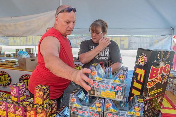Kurt Pearson grabs a box of fireworks as Penny Pearson uses an app on her phone to see what the fireworks will look like at the Knights of Columbus tent in a parking lot on Highway 169. Kurt said they thought about going to Iowa to buy fireworks, but wondered about the quality since it is the first year the state has allowed bigger fireworks to be sold. Photo by Jackson Forderer
