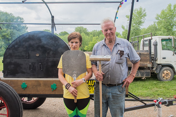 Vusa Bentley (left) and Jack McGowan do their best American Gothic impression in front of a mobile brick pizza oven that they built at McGowan's farm. Photo by Jackson Forderer