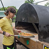 "Vusa Bentley takes a gluten-free vegetarian pizza out of a mobile brick oven that she and Jack McGowan built at McGowan's farm. Bentley said of the mobile oven, ""Seeing this in action brought happy tears to my eyes."" Photo by Jackson Forderer"