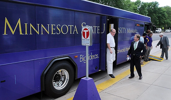 John Cross<br /> Minnesota State University administration and staff check out a new city bus wrapped in school colors and displaying the student logo on Tuesday. Four more buses wearing the wrap will hit the streets in coming weeks.
