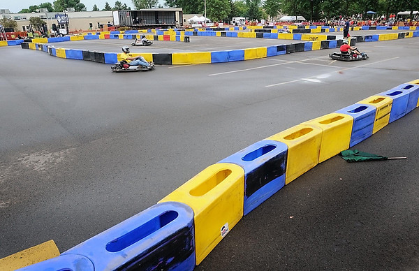 Racers whiz around a race track created by plastic barriers set up in an MRCI parking lot Saturday during the running of the seventh annual MRCI Grand Prix.