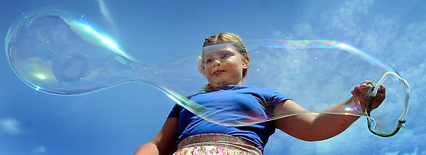 John Cross<br /> Alexandria Anton-Drumm stretches out a king-sized bubble at a booth that was part of North Mankato's Blues on Belgrade, Saturday.