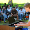 Pat Christman<br /> Karl Krenz plays the piano for people sitting under a shade tree at the Sibley Park bandshell during a Picnic in the Park variety show Tuesday. The show featured local artists and audience-written haiku poetry. A second Picnic in the Park is planned for Aug. 19 at North Mankato's Wheeler Park.