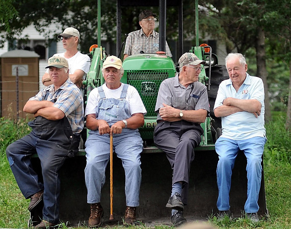 John Cross<br /> A tractor was turned into an impromptu grandstand for some men who were more interested in observing the action rather than bidding on at the late Vern Peterson's auction on Saturday near Amboy.
