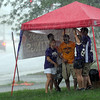 Pat Christman <br /> Minnesota Vikings fans take refuge from a rain shower under a canopy at the Dairy Queen on Stoltzman Road at one of four tailgate parties welcoming the team to their training camp Thursday.