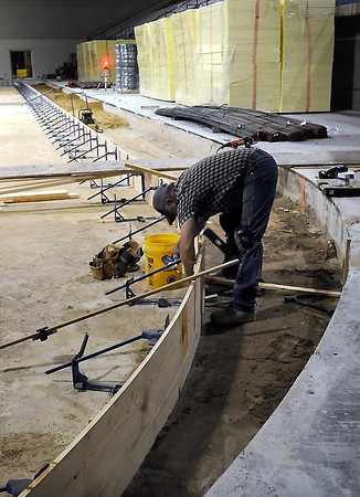 John Cross<br /> A worker sets forms up that define the footprint of the, slightly smaller hockey rink that is being installed in the Verizon Wireless Center. The curved concrete behind him defines the edges of the original ice sheet. The project which includes new seating and dasher boards is expected to be completed by the end of August.
