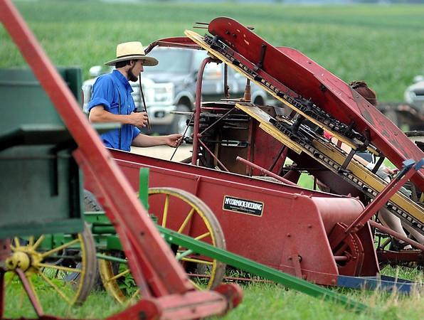 John Cross<br /> A young Amish farmer inspects some of the horse-drawn machinery that was to be auctioned off.