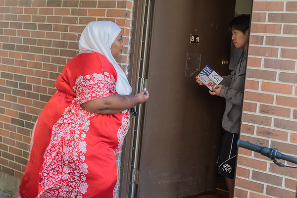 Fardousa Jama (left) talks to a resident at the Highland Hills apartment complex while campaigning door-to-door on Saturday. Jama is the first Somali woman to run for any local government office in Mankato. Photo by Jackson Forderer
