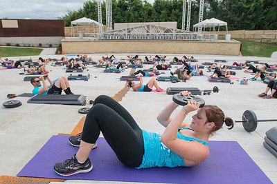 Leslie Busch, an instructor with the YMCA, lifts a weight during an exercise as part of Pump in the Park held at Vetter Stone Amphitheater. Two classes were led by YMCA instructors at the park on Thursday evening. Photo by Jackson Forderer