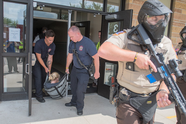 Mankato fire fighters carry out a fake victim of a fake school shooting at Washington Elementary while being escorted out of the building by a Blue Earth County deputy sheriff (right) at a training session held on Wednesday. Photo by Jackson Forderer