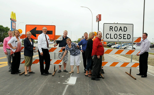 Representives from businesses most affected by construction of the Adams Street-Highway 22 roundabout pose for a group photo before they removed the barricades to officially open it to traffic on Friday at 6 p.m.<br /> Photo by John Cross