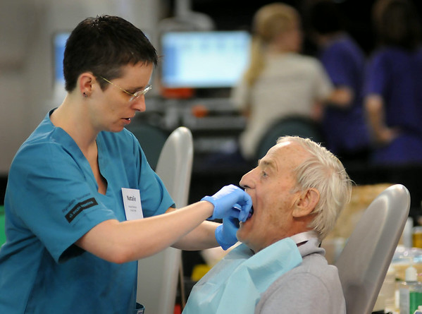 Dentist Natalie Peterson of Duluth fits Jim Campbell of Minneapolis for a partial during the Mission of Mercy. Photo by John Cross